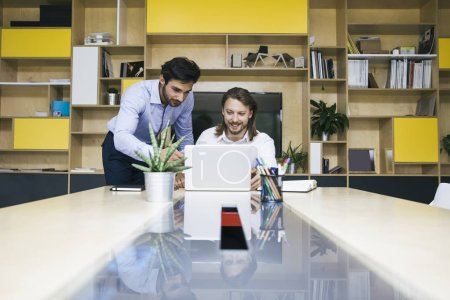 Foto de Dos jóvenes empresarios que trabajan en el ordenador portátil en la oficina - Imagen libre de derechos
