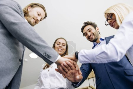 Photo for Young coworkers putting hands together as symbol of unity in the office - Royalty Free Image