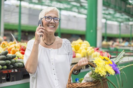 Photo for Portrait of senior woman buying on market,  holding basket with flowers and using mobile phone - Royalty Free Image
