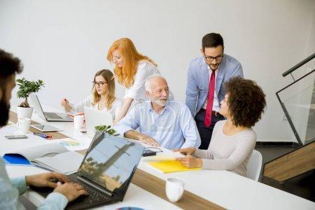 Photo pour Découvre au groupe jeune multiraciale des gens d'affaires autour de table au cours de la réunion du personnel au bureau - image libre de droit