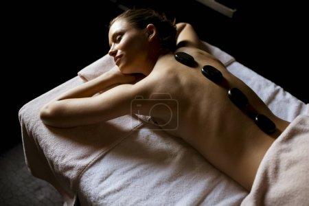 Photo pour Jolie jeune femme ayant une thérapie de massage aux pierres chaudes - image libre de droit