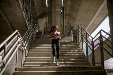 Foto de Mujer joven gimnasio hacer ejercicios al aire libre en entorno urbano - Imagen libre de derechos