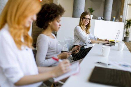 Photo pour Jeunes femmes travaillant dans les bureaux modernes - image libre de droit