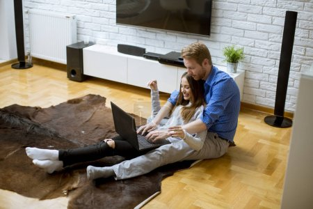 Photo for Close up view at young couple using laptop while sitting on the floor in their living room - Royalty Free Image
