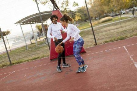 Foto de Grupo de jóvenes multiétnicos jugando al baloncesto en la cancha - Imagen libre de derechos