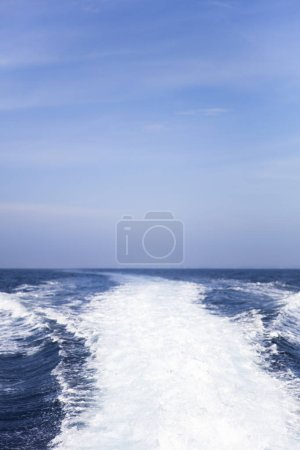 Photo for Water splash behind the  speed boat in the ocean with beautiful blue sky - Royalty Free Image