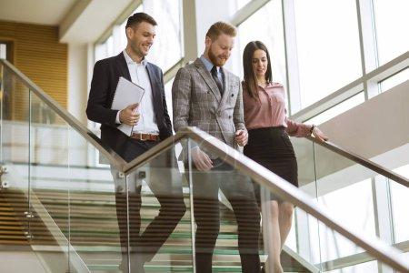 Photo pour De jeunes partenaires analysent les résultats de l'entreprise en descendant les escaliers dans un bureau moderne - image libre de droit