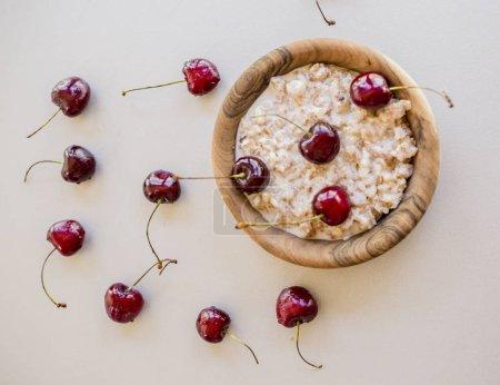 Fresh ripe bird cherries with porridge close up shot