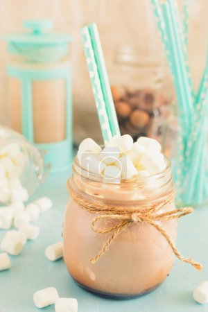 In the foreground of photos with a jar of hot cocoa and cocktail straws. In the background scattered marshmallows, turquoise coffee pot and sweets. Background in bokeh. Beautiful picture in high key.