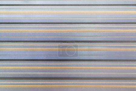 Photo pour Texture de la clôture en métal ondulé. Fond vide avec bandes horizontales parallèles. Le mur est gris et beige . - image libre de droit