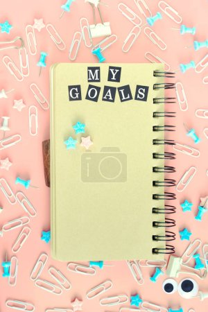 Notepad with brown pages, on springs. The inscription My Goals. The stationery is in disarray. Staples, paper clips and asterisks are randomly scattered on a pink background.