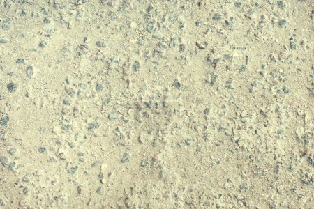 Texture of worn asphalt, gravel is seen. Empty old road surface background.