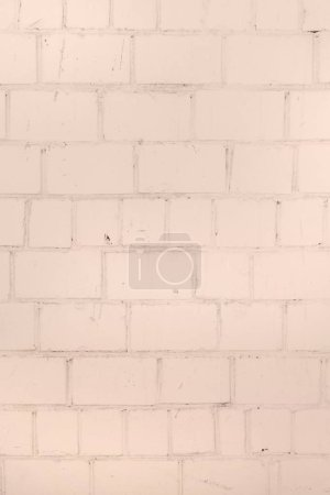 Wall of bricks painted with a pale peach paint. Texture of masonry. Blank background.