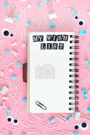 Notepad on springs with white pages. The inscription My Wish List. Stationery is in disarray. The asterisks and puppet eyes are chaotically scattered on a pink background.
