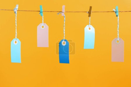 On a bright orange background photographed labels. Five multicolored empty labels hang on a rope pinned with clothespins. Bright layout, mock up.