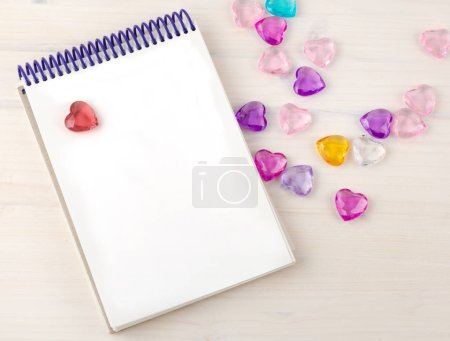 Blank notepad on spirals. Place for text. Around colored decorative hearts. Mok up