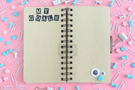 Notepad on springs with brown pages. The inscription My Goals. Stationery is in disarray. The asterisks and puppet eyes are chaotically scattered on a pink background. Bright photo from the top.
