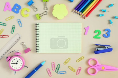 On a beige background lies an empty notebook with a place for inscriptions. Around it are various colored pencils, scissors, paperclips. Background of school subjects. Bright photo.