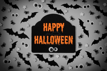 A lot of decorative bats, asterisks and puppet eyes are lined with a gray background. In the center there is a figured tablet with an inscription. Happy Helloween written in bright orange letters.