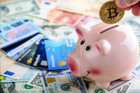 Man putting golden bitcoin coin in piggy bank  - symbol of crypt