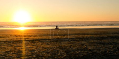 Photo for Bicyclists riding during sunset at Westport Lighthouse beach near West Ocean Avenue entry to beach - Royalty Free Image