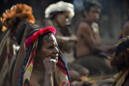 BALIEM VALLEY, WEST PAPUA, INDONESIA, JUNE 16th, 2016: Close up Portrait of adult woman in the traditional headdress of bird feathers. Dugum Dani tribe people. New Guinea, Indonesia,June 16, 2016