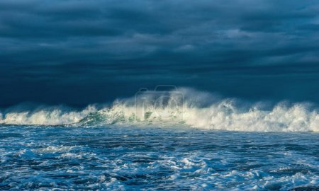Photo for Powerful ocean wave on the surface of the ocean. Wave breaks on a shallow bank. Stormy weather, clouds sky background. Seascape. - Royalty Free Image