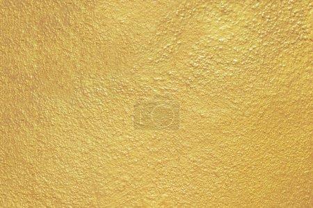 Foto de Fondo de textura de pared de oro. Amarillo brillante pintura de oro en la superficie de la pared de hormigón, vibrante fondo de pantalla de lujo dorado - Imagen libre de derechos