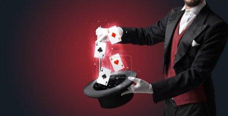 Photo pour Magicien avec des gants blancs évoquant des cartes à jouer d'un cylindre avec baguette magique - image libre de droit