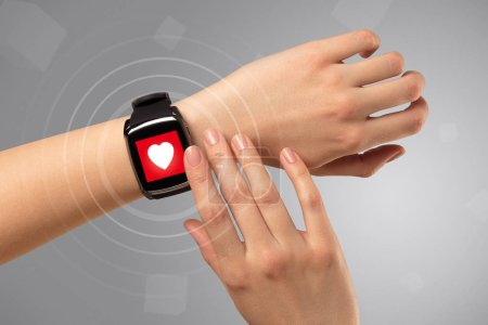 Photo for Naked female hand with smartwatch and with heart rate icon on the watch - Royalty Free Image