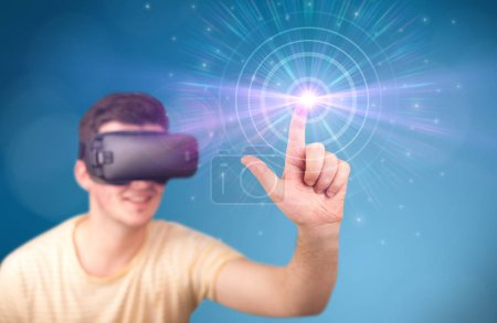 Photo for Young impressed man wearing virtual reality goggles with blue circles around his finger - Royalty Free Image