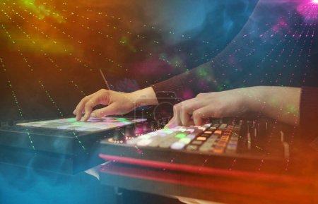 Photo pour Mélange de musique sur contrôleur dj avec les couleurs du club parti autour à la main - image libre de droit