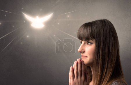 Photo for Young woman praying on a grey background with a sparkling bird above her - Royalty Free Image