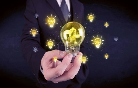 Photo for A creative businessman has a bright idea concept with office worker holding light bulb in foreground. - Royalty Free Image
