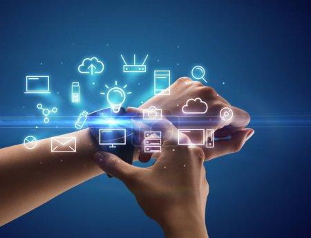 Photo pour Gros plan main féminine avec smartwatch et symboles multimédia autour et fond bleu - image libre de droit