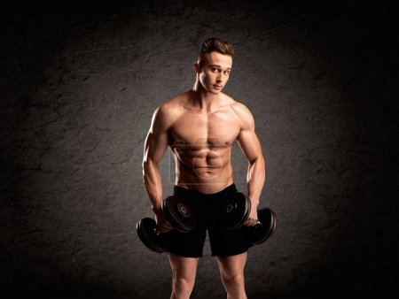 Photo for A handsome fitness guy lifting weight and showing his strong muscles in front of a black urban concrete wall concept - Royalty Free Image