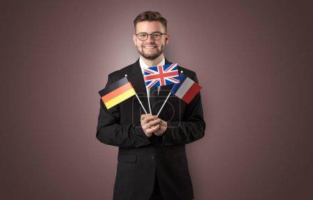 Photo pour Étudiant joyeux debout devant le mur avec le drapeau national sur la main - image libre de droit