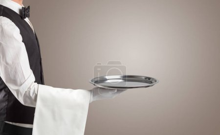 Photo for Waiter serving with white gloves and steel tray in an empty space - Royalty Free Image