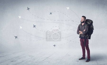 Photo for Handsome young man standing with a backpack on his back and little planes in the background - Royalty Free Image