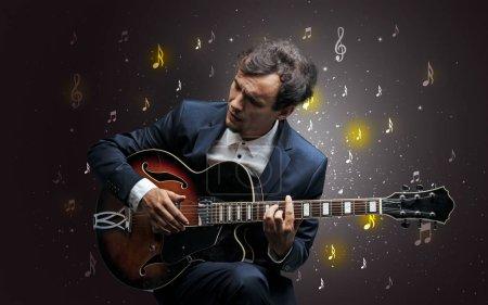 Photo pour Jeune guitariste avec chute musical notes papier peint et le concept classique - image libre de droit