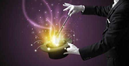 Foto de Mano de mago conjurar con la varita de luz de un cilindro negro - Imagen libre de derechos