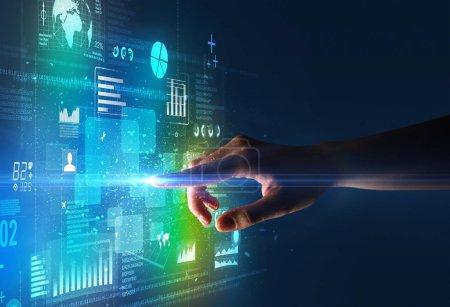 Photo pour Doigt féminin touchant un faisceau de lumière entouré de données et de graphiques bleus et verts - image libre de droit