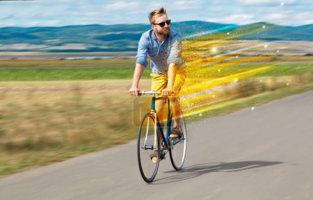 Photo for Young riding bicycle in fabulous nature with high speed - Royalty Free Image