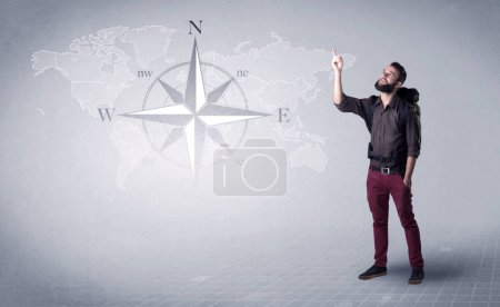 Photo for Handsome young man standing with a backpack on his back and a compass and a world map in the background - Royalty Free Image