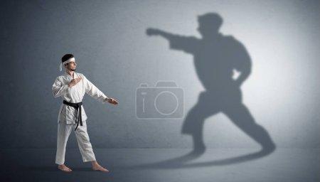 Photo pour Jeune homme karaté confronté à sa propre ombre - image libre de droit