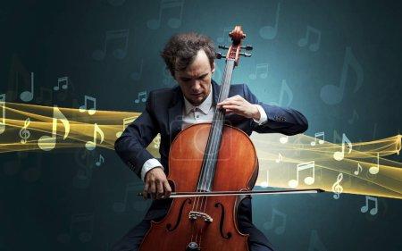 Photo pour Jeune mâle musicien jouant sur son violoncelle avec des notes de musique autour de - image libre de droit