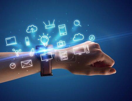 Photo pour Bouchent femelle main avec smartwatch et symboles multimédias autour et fond bleu - image libre de droit