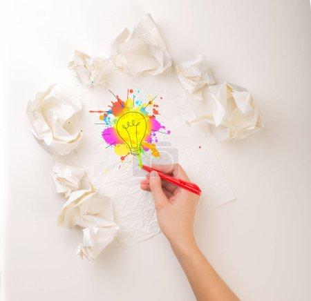 Photo pour Main féminine à côté de quelques boules de papier froissées dessinant une ampoule colorée - image libre de droit