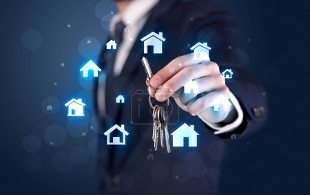 Photo for Businessman in suit holding keys with house graphics around and dark background - Royalty Free Image