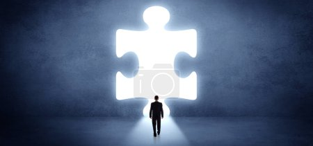 Photo for Businessman  standing and looking to a big puzzle piece - Royalty Free Image